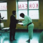 Man in Taekwon-Do uniform bowing and receiving a certificate from a man in a suit.