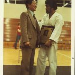 Man in suit with man in Taekwon-Do uniform facing each other.