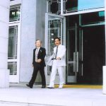 Two man in suits walking out of an official building.