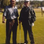 Two men in golf attire with clubs on a golf course.