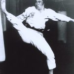 Man performing a kick on a kicking bag.
