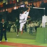 Girl in Taekwon-Do uniform jumping and kicking a board above her head at a competition.