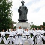 Group of Taekwon-Do students posing in a stance in front of a Korean monument.