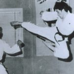 Man in Taekwon-Do uniform demonstrating a flying kick with a partner.