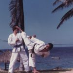 Man in Taekwon-Do uniform demonstrating a kick with a partner in front of palm trees and water.