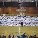 Large group of Taekwon-Do colour belt and black belt students posed for photo with man in suit.