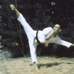 Young man doing a kick in a Taekwon-Do uniform.
