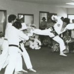 Man in Taekwon-Do uniform breaking multiple boards with a kick.