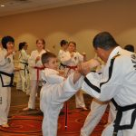 Taekwon-Do instructor helping young student correct his foot placement for a kick.