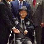 Three men in suits standing behind a fourth man in a wheelchair.