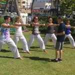 Group of martial artists training on grass in sun.