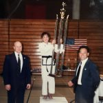 Girl in Taekwon-Do uniform holding large trophy on podium in between two men in suits.