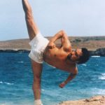 Man in white shorts kicking vertically in the air.