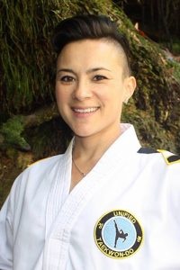 "Young Korean-American woman in Taekwon-Do uniform with patch that reads ""Unified Taekwon-Do"""